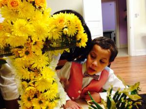 My oldest getting tutored in placing the flowers in the Easter Cross of Living Flowers, Easter 2013.